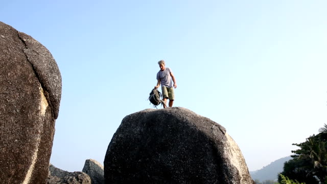 Wanderer steht auf jungle boulder, looks an
