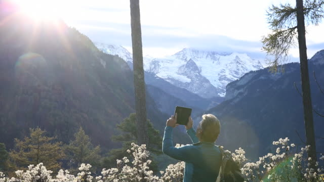 Hiker takes picture with digital tablet, mountain sunrise