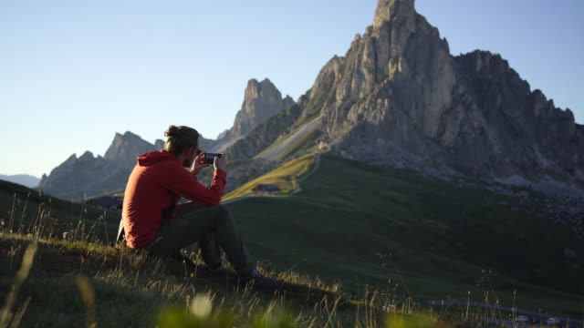 vidéos et rushes de hiker taking a photo in the dolomites while sitting in the grass - photophone