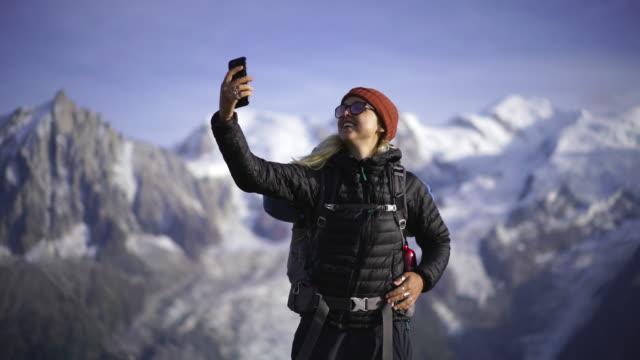 vidéos et rushes de randonneur prenant un selfie près du mont blanc - s'évader du réel