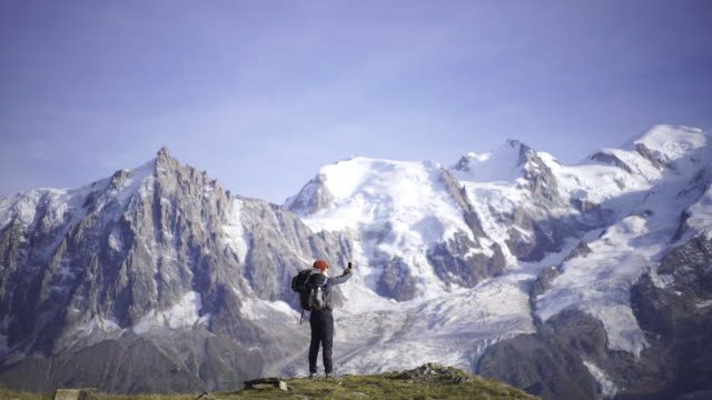 hiker taking a selfie near mont blanc - photographing stock videos & royalty-free footage