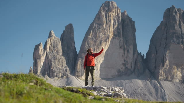 hiker taking selfie in the dolomites at sunset - sonnenbrille stock-videos und b-roll-filmmaterial