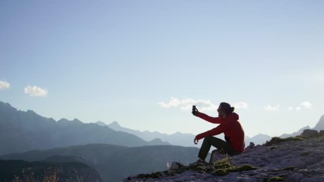 escursionista che si fa selfie sulle dolomiti al tramonto mentre è seduto su una roccia - ricordi video stock e b–roll