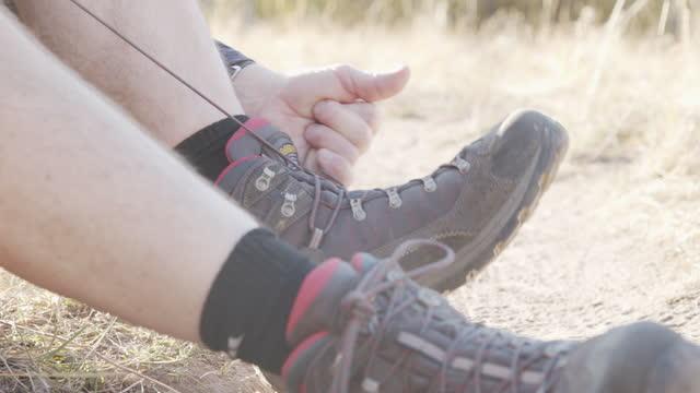 ハイカーは美しい9月の秋の色でグランドジャンクションコロラド近くのグランドメサ国有林での冒険に彼のハイキングブーツに靴ひもを結びます - 国有林点の映像素材/bロール