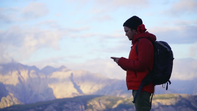 hiker using cell phone while stopped in the dolomites - rucksack stock videos & royalty-free footage