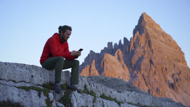 hiker using cell phone while stopped in the dolomites with glowing peak behind - one mid adult man only stock videos & royalty-free footage