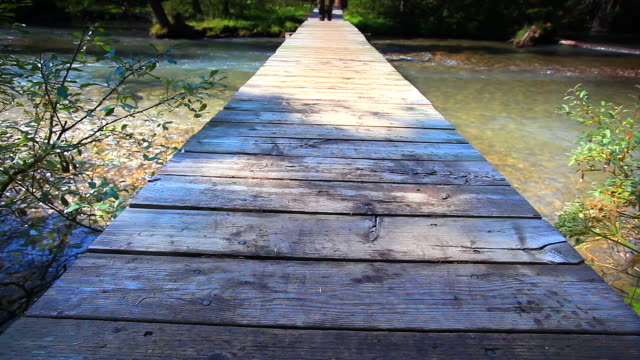 hiker walking across wooden bridge - low section stock videos & royalty-free footage