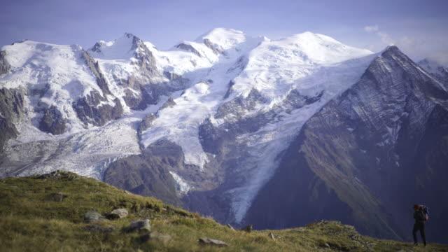 stockvideo's en b-roll-footage met wandelaar wandelen langs een pad in de buurt van de mont blanc - stilstaande camera