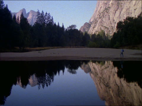 hiker walking along lake with trees and mountains in background / yosemite national park, california - 2001 stock-videos und b-roll-filmmaterial