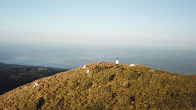 stockvideo's en b-roll-footage met hiker walking down the edge of a mountainside - cres kroatië