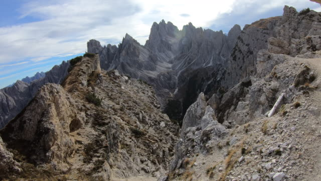 vidéos et rushes de hiker walking in narrow footpath with the sharp dolomite mountains in the italian alps from top of a hill. - vertige