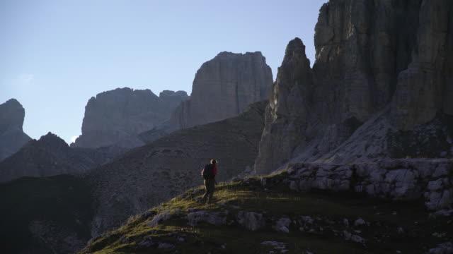 escursionista che sale su una collina nelle dolomiti - tranquility video stock e b–roll