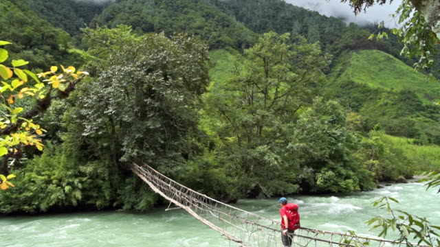 A hiker walks across a narrow, wooden foot bridge in the remote jungle of Myanmar