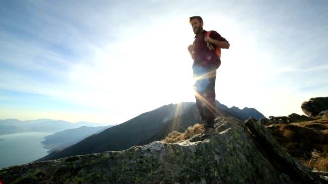Hiker walks along mountain ridge crest at sunset