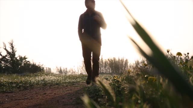 vídeos de stock e filmes b-roll de hiker walks along rural track, looks out to sunrise - só um homem maduro