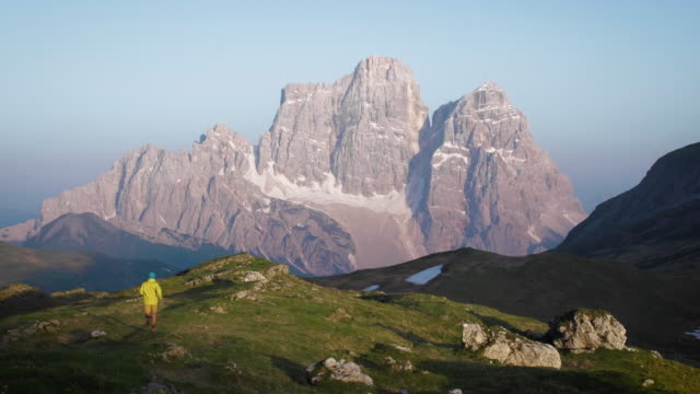 hiker walks down alpine meadow ridge at sunrise - inquadratura fissa video stock e b–roll