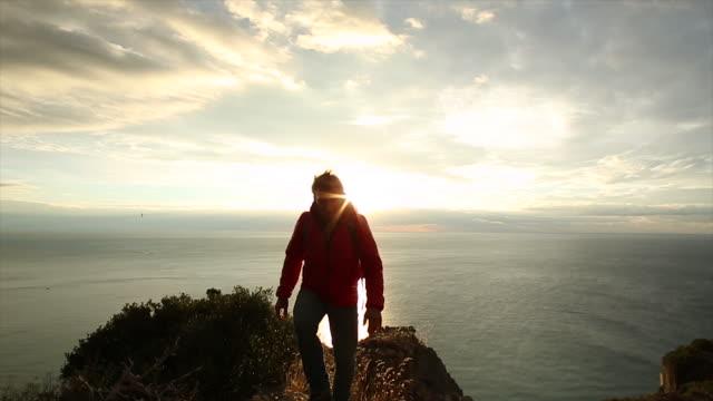 Hiker walks from cliff edge above sea, sunrise