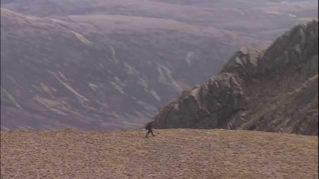 a hiker walks on a cliff in the highlands of scotland. - valley stock videos & royalty-free footage