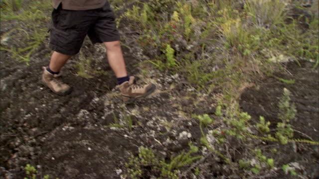vídeos de stock, filmes e b-roll de a hiker walks on a rugged mountain trail. - calção