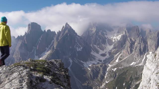 vídeos de stock e filmes b-roll de hiker walks out to promontory, clouds hang on distant peaks - coberto de neve