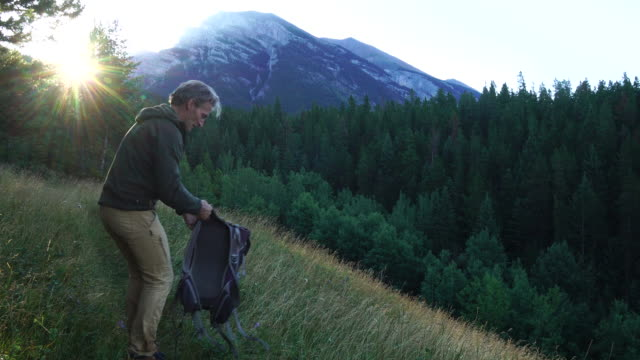 hiker walks through meadow, removes digital tablet to check direction - rucksack stock videos & royalty-free footage