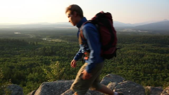 vídeos y material grabado en eventos de stock de hiker walks to edge of rock cliff, look down and across valley - sólo hombres jóvenes