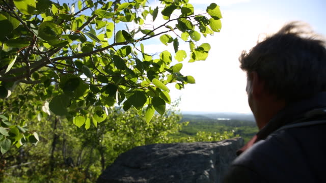 vidéos et rushes de hiker walks to edge of rock cliff, looks across valley - un seul homme d'âge moyen