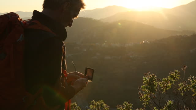 Hiker walks to viewpoint, takes compass reading over hills, sunrise
