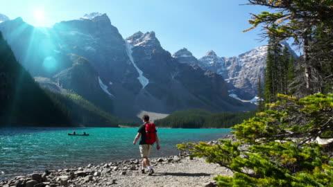 wanderer geht in richtung lake in the mountains. - banff nationalpark stock-videos und b-roll-filmmaterial