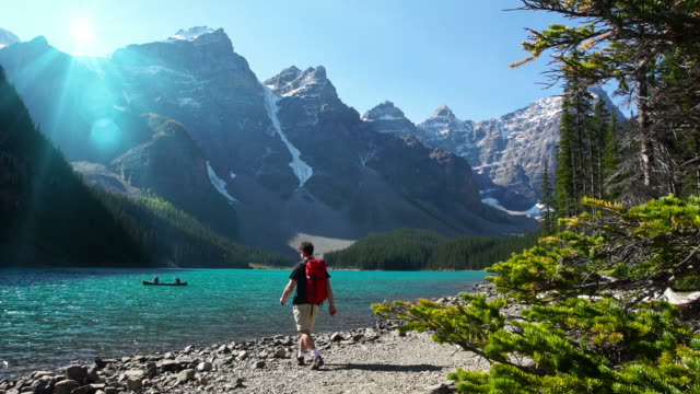 hiker walks toward lake in the mountians - banff national park stock videos & royalty-free footage