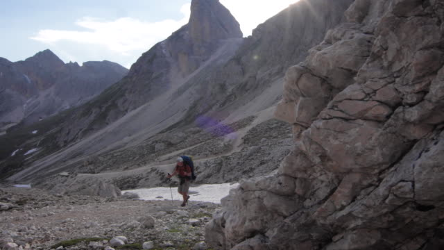 hiker walks up rugged mountain path, prominent peaks behind - maglietta video stock e b–roll