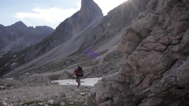 wanderer geht auf zerklüfteten bergpfad, markante gipfel hinter - t shirt stock-videos und b-roll-filmmaterial