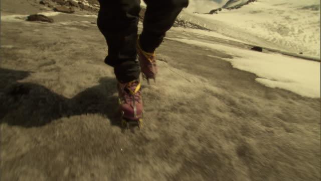 vidéos et rushes de a hiker wearing spiked boots walks across a gray icy mountainside. - chaussures