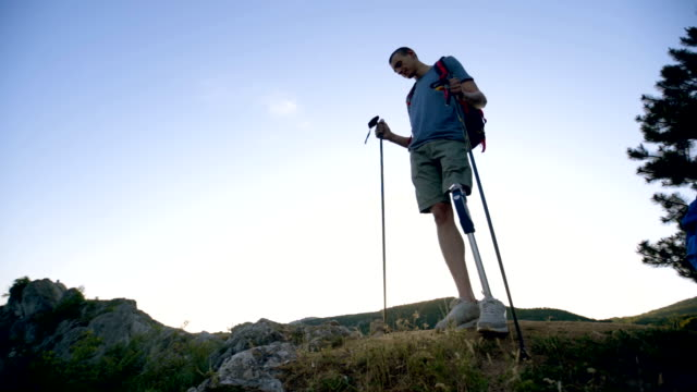 hiker with artificial limb on top of the mountain - disability stock videos & royalty-free footage