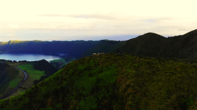 vidéos et rushes de hiker with yellow raincoat in the viewpoint with volcanic crater in the azores islands. - îles de l'atlantique
