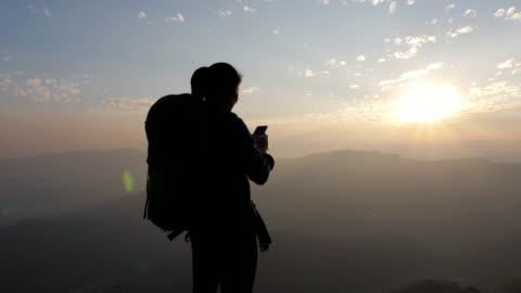 wanderer-frau mit handy für nehmen sie ein foto auf der oberseite berg im sonnenuntergang, dolly bewegung, slow-motion - klippe stock-videos und b-roll-filmmaterial