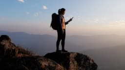 Hiker woman using mobile phone for take a photo on the top of mountain in sunset time , dolly movement , slow motion