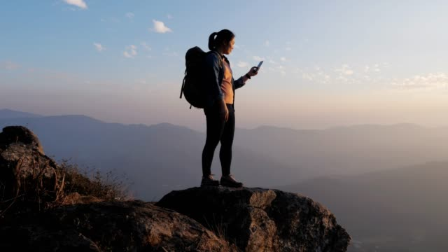 hiker woman using mobile phone for take a photo on the top of mountain in sunset time , dolly movement , slow motion - scoperta video stock e b–roll