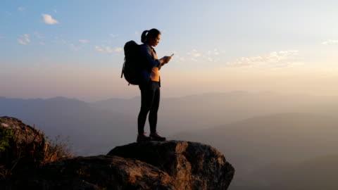 stockvideo's en b-roll-footage met wandelaar vrouw met behulp van mobiele telefoon op de top van de berg, communicatie - fotografische thema's