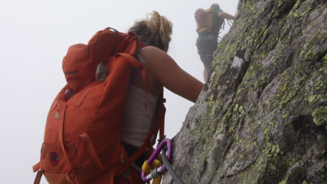 hikers ascend vertical via ferrata route into mist - metal clip stock videos and b-roll footage