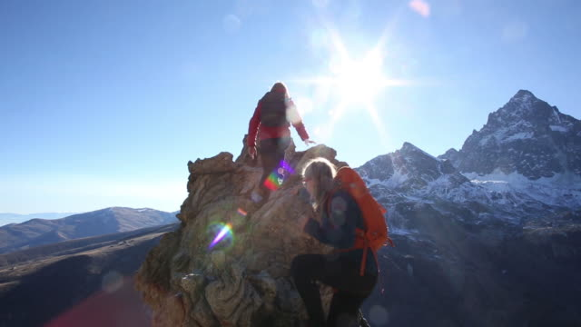 Hikers ascends mountain pinnacle, above snowy mtns