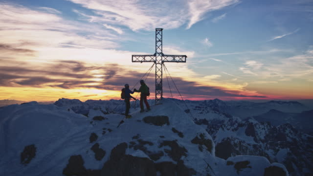 hikers at summit cross on mountaintop against sky - austria stock videos & royalty-free footage