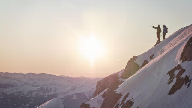 wanderer jubeln auf gipfel des schneebedeckten berges - mit dem finger zeigen stock-videos und b-roll-filmmaterial