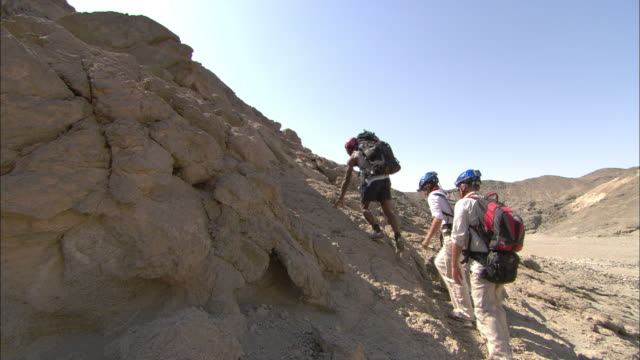 hikers climb up a rocky hillside at an archaeological site in egypt. - traditional helmet stock videos and b-roll footage