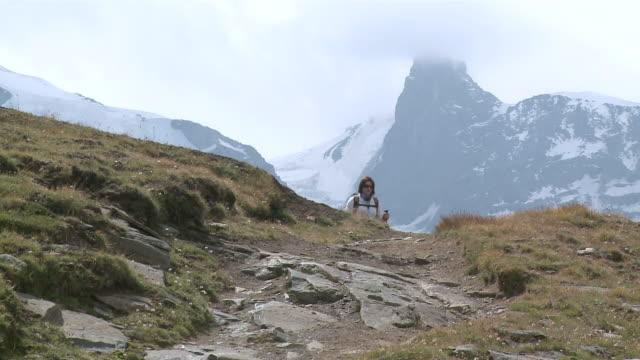vídeos y material grabado en eventos de stock de ms hikers climbing and walking on mountain at front of riffelberg / zermatt, valais, switzerland - bastón de senderismo