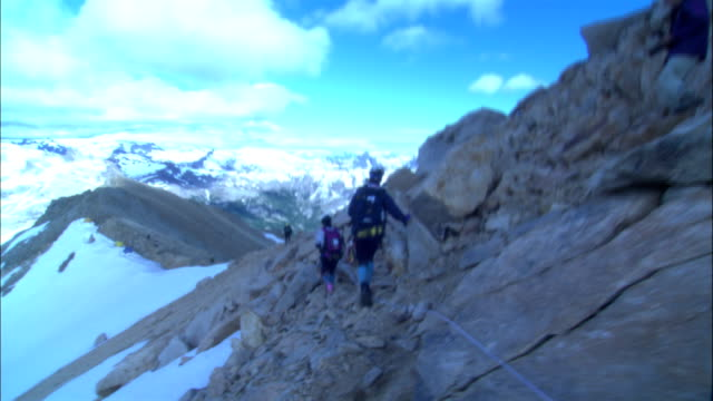 hikers cross a treacherous mountain ridge. - provincial reconstruction team stock videos & royalty-free footage