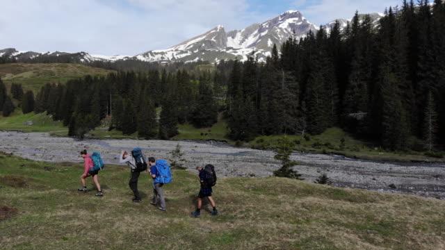 wanderer durchqueren alpine feld in schweizer bergen - wandern stock-videos und b-roll-filmmaterial