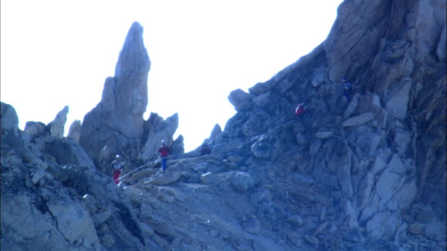 hikers descend a steep, mountain ridge. - provincial reconstruction team stock videos & royalty-free footage
