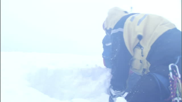 hikers dig a shelter in the snow as they try to survive a blizzard. - hypothermia stock videos and b-roll footage