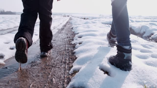 hikers in boots walking on snowy, slushy winter road, super slow motion - wet stock videos & royalty-free footage